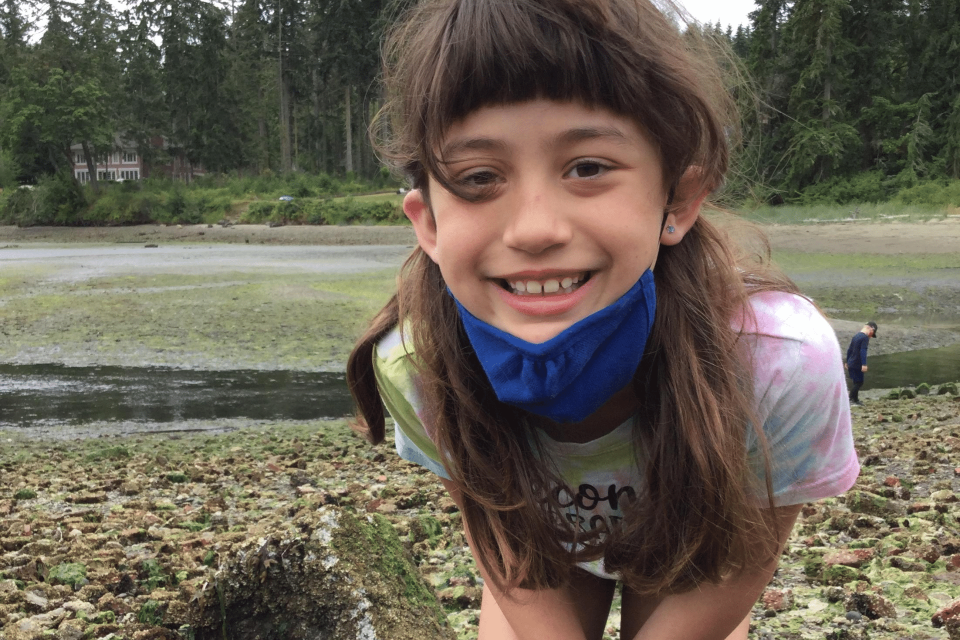 A child smiles while at Blakely Harbor on Bainbridge Island during an IslandWood summer camp. They have pulled their mask down to their chin.