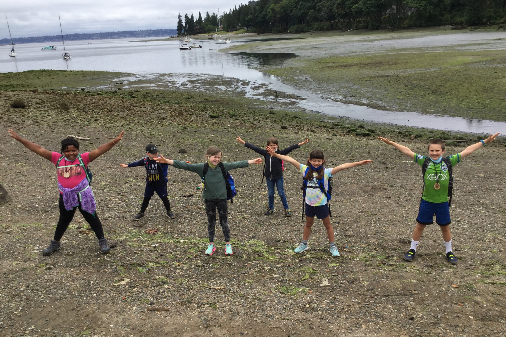 Campers stand with their arms outstretched to demonstrate social distancing at Blakely Harbor.
