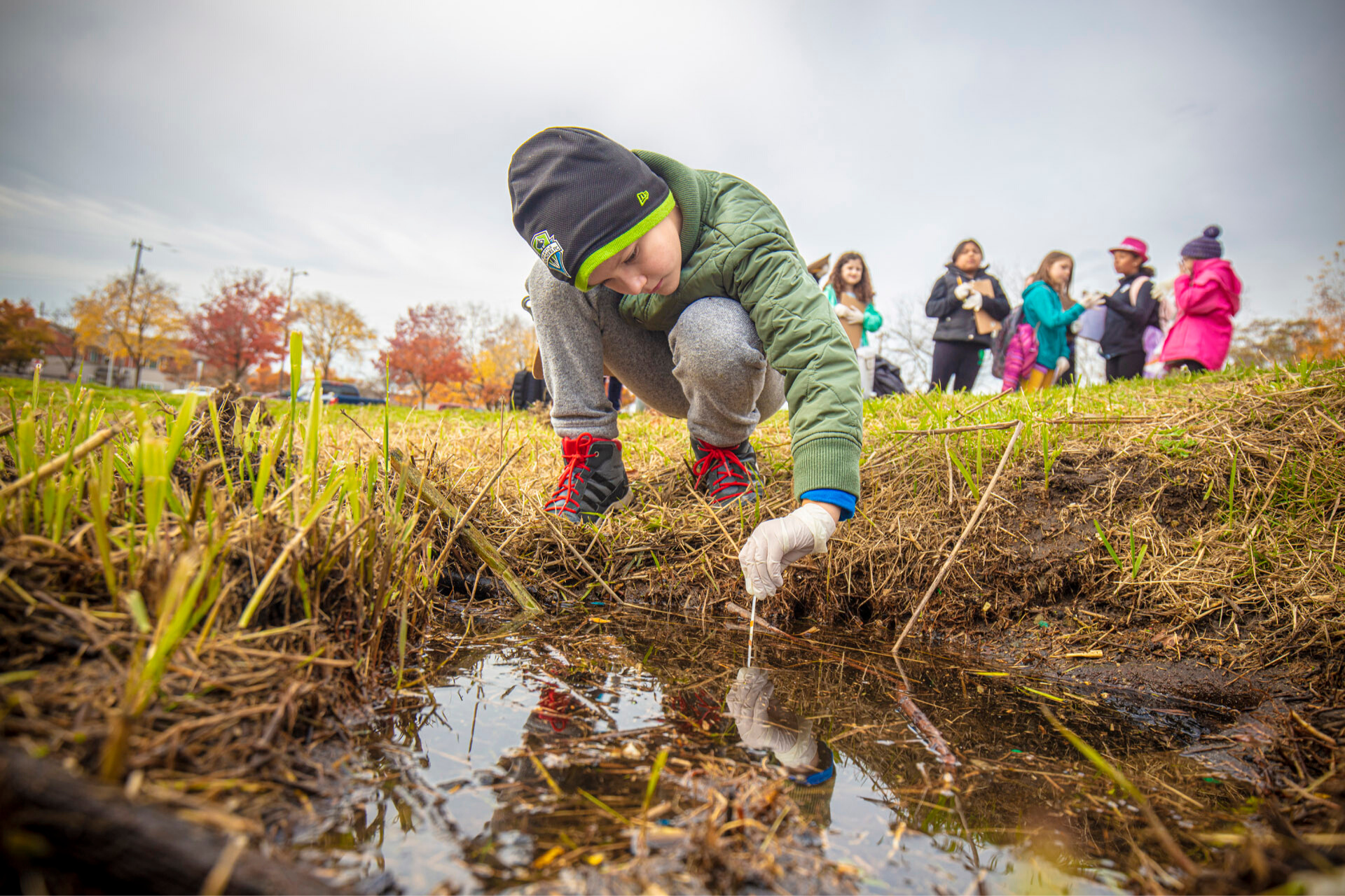 A child kneels to examine a puddle during an IslandWood program in Seattle. A group of other children are visible in the background.