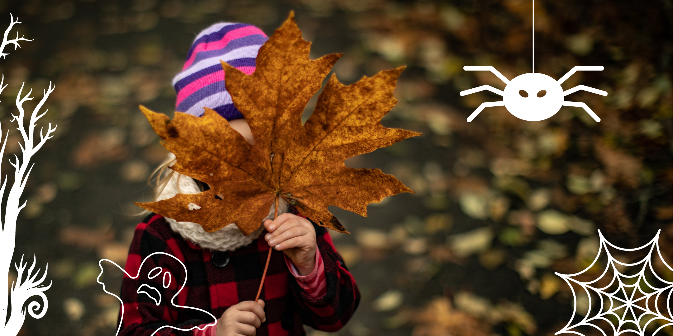 A child holds a large maple leaf up to their face. Halloween-themed illustrations, including a tree, ghost, cobweb, and spider, are overlaid on the image.